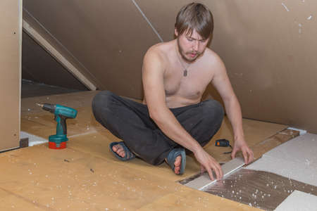 Man is making thermal insulation in the attic