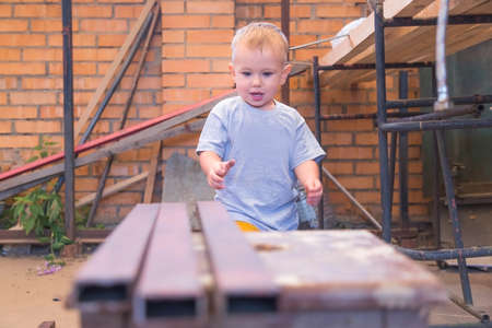 Boy is playing with iron building materials near the garage while parents don't see him. Renovation and construction at home. He wants to help his father.