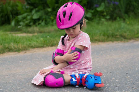 A little girl roller skating in full protection fell on the asphalt. The concept of an active healthy lifestyle and safe riding. Imagens