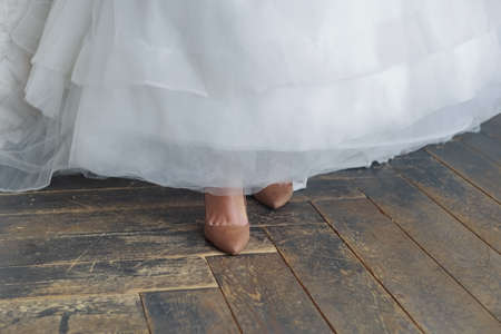 Bride's feet in old non-wedding shoes. I forgot to change my shoes. The hem of the dress is raised. The old shabby floor is visible.
