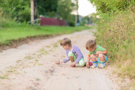 Children draw with a stone on the sand while squatting on a sandy village road.soft focus, selective focus