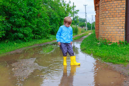Child in rubber boots and raincoat playing in a puddle
