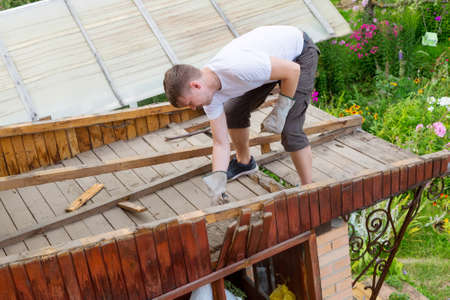 The man knocks an old rotten wooden plank with a hammer from the parsing of the roof. Dismantling the roof, house renovation.