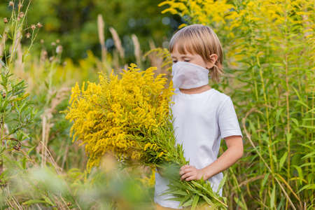 .A little girl in a medical mask holds a huge bouquet of yellow autumn flowers in a field. Coronavirus prevention, keep social distance and keep wearing masks