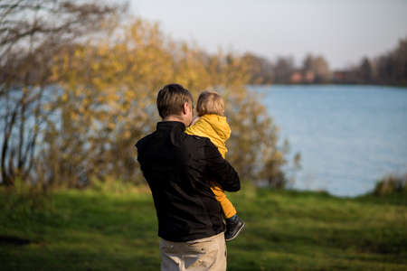 Dad holds his son in a yellow jacket in his arms, they stand with their backs to the camera and look at the lake. Autumn park, Indian summer.