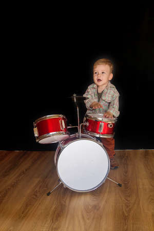 Two year caucasian boy is Playing Drum Set Isolated on Black Background. Stockfoto