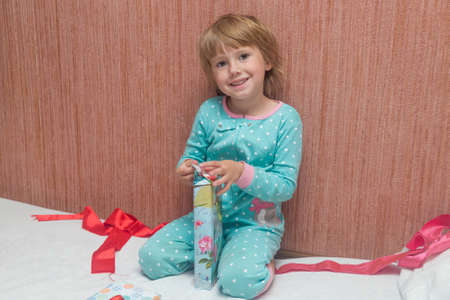 Adorable little Child unpacks gifts sitting on the bed