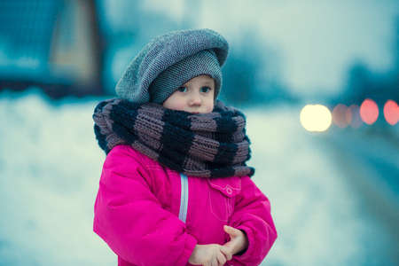 .A little girl stands in the snow by the road in the evening