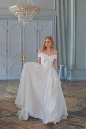The bride in a beautiful white wedding dress enters the hall holding the hem of the dress