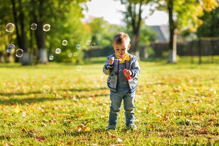 A little boy in denim clothes blows bubbles in the autumn park.