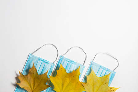 Autumn fallen leaves and medical masks on a white background.