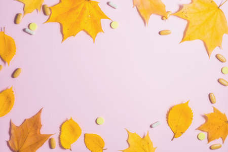 Autumn fallen leaves and medicines on pink background