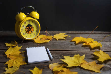 .Still life of autumn fallen leaves and office supplies on a wooden background.