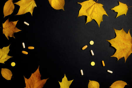 Autumn fallen leaves and medicines on black background