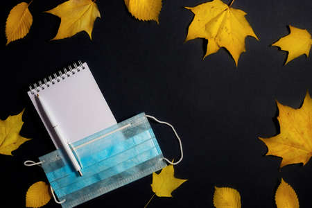 .Autumn fallen foliage, notebook and medical mask on black background.