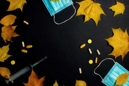 Autumn fallen leaves and medical masks and medicines on black background 写真素材