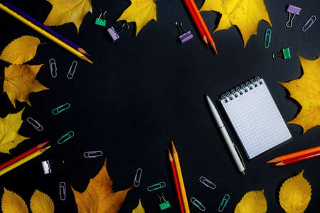 .Autumn fallen foliage and stationery on black background