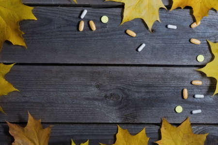 .Autumn foliage and medicines on wooden background.