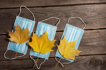 .Autumn fallen leaves and medical masks on wooden background