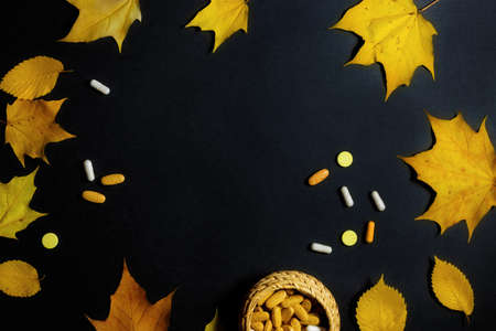 Autumn fallen leaves and medicines on black background.