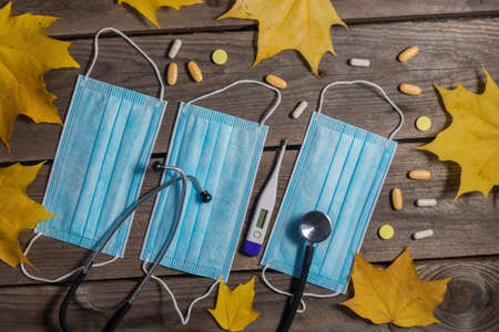 .Medical masks, stethoscope and thermometer on wooden background.