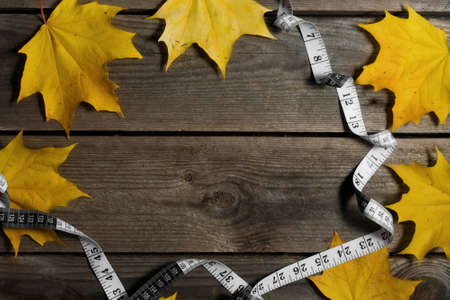 Autumn fallen leaves and measuring tape on wooden background