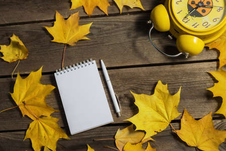 .Autumn fallen leaves and office supplies on wooden background