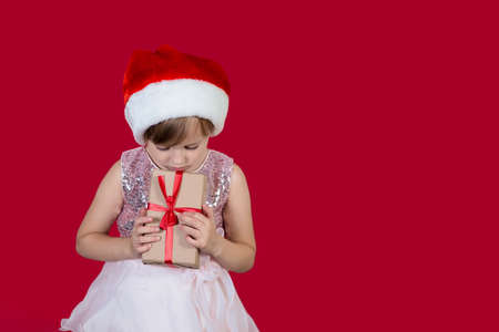 Beautiful cute caucasian little girl in santa hat holding a present to her chest sad maybe her christmas is ruined isolated on red background.