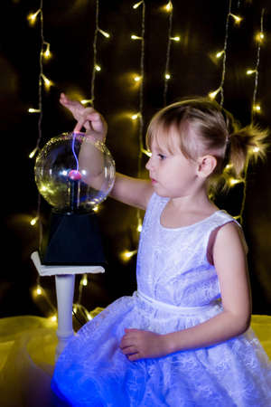Cute little Child girl holding witch crystal ball with lightning and electricity over dark background with garlands bokeh