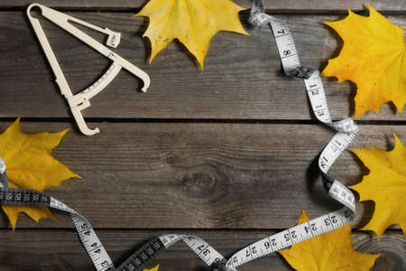 Autumn fallen leaves, measuring tape and caliper on wooden background