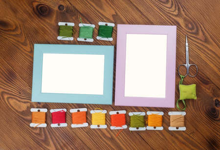 Wooden frames for cross stitch embroidery for designer mockup on wooden background