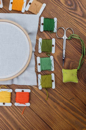 Cross stitch hoop with stretched canvas on wooden background with copyspace Stockfoto