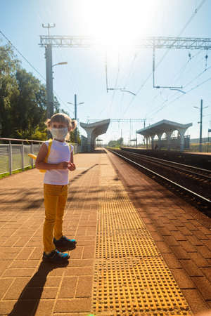 Little girl in a T-shirt and jeans and a medical mask waiting for the train