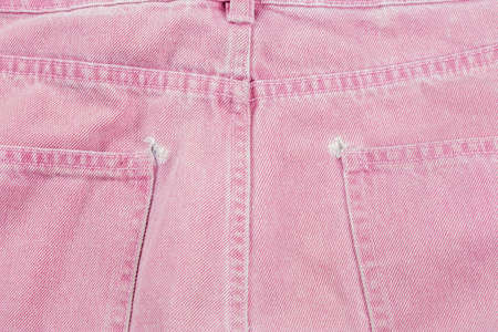 A close-up of a frayed pink jeans pocket, a torn off pocket.