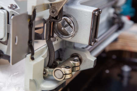 Parts and components of an industrial sewing machine tilted to one side during repair and maintenance