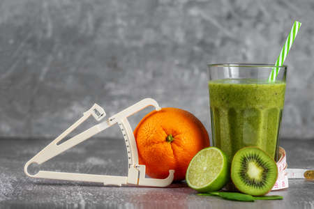 Fresh smoothie drink in a tall glass glass with centimeter wrapped around it and a caliper next to it, surrounded by fruits on a gray concrete background. The concept of proper nutrition, weight loss