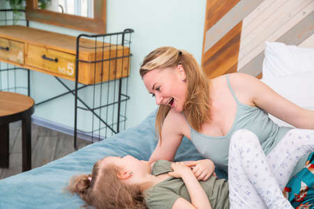 Portrait of mother with her preschool-aged caucasian daughter lying on the bed in the bedroom, smiling at each other, having fun and having a good time with children at home.