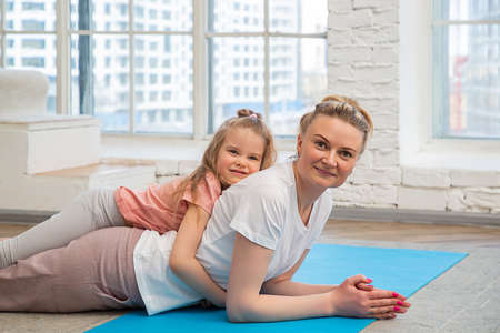 Portrait of mother with her preschool-aged caucasian daughter in sportswear lying on a yoga mat in front of living room window, hugging and looking at the camera. Spending time with children at home.