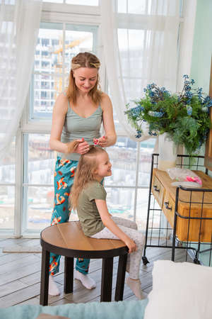 Portrait of mother combing her preschool-aged caucasian daughter sitting on a chair in front of the mirror in the bedroom