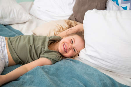 Portrait of preschool-aged caucasian girl lying on the bed and fooling around smiling looking at the camera