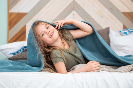 Portrait of preschool-aged caucasian girl lying on the bed and fooling around under the covers smiling looking at the camera