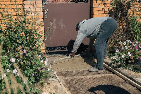 Eldery man spreads a cement mixture with a wooden block on a garden path, construction work in a garden plot Foto de archivo