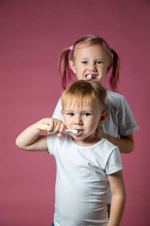 Smiling caucasian little boy and girl cleaning his teeth with electric sonic and manual toothbrush on pink background.