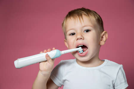 Smiling caucasian little boy cleaning his teeth with electric sonic toothbrush on pink background.