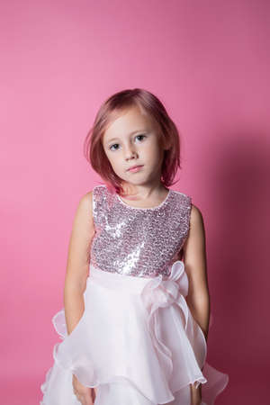 Little caucasian girl in a festive dress with sequins posing on a pink background looking at the camera Foto de archivo