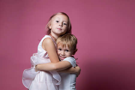 Caucasian brother and sister, hugging on camera on pink background studio shot. Family ties, friendship, happy childhood concept. Foto de archivo