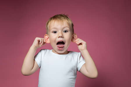 Caucasian boy 3 years old makes faces, shows tongue, looking at camera on pink background