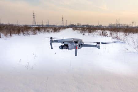 Quadcopter drone flying over a snowy field in winter. Foto de archivo