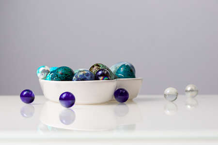 Easter blue quail eggs in a plate in the shape of a heart on a white table.