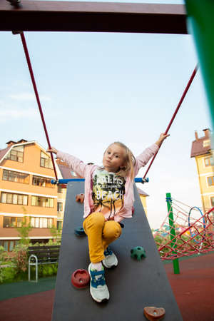 Caucasian girl climb the climbing wall in the playground.